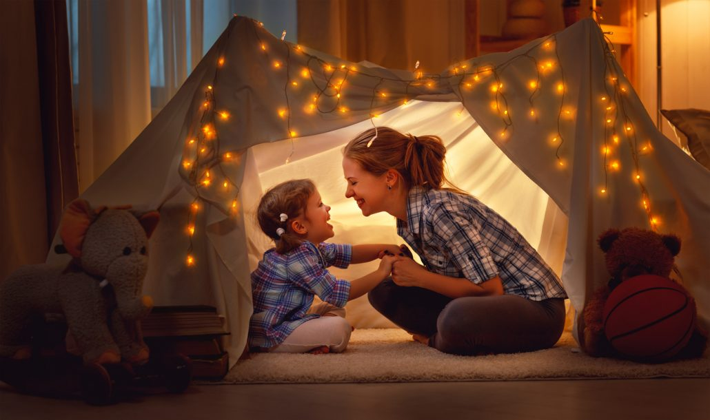 A mother and daughter playing at home in a tent.