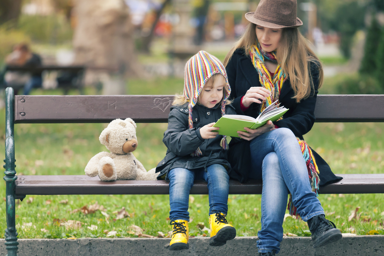 Woman who acts as foster as a single parent reading to foster child at park in fall