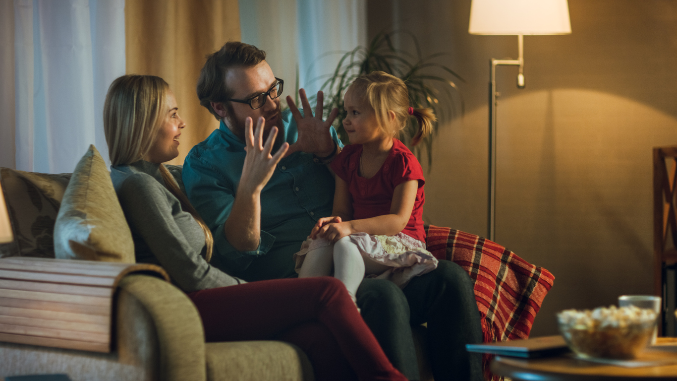 Foster parents telling their foster child a story on the couch.