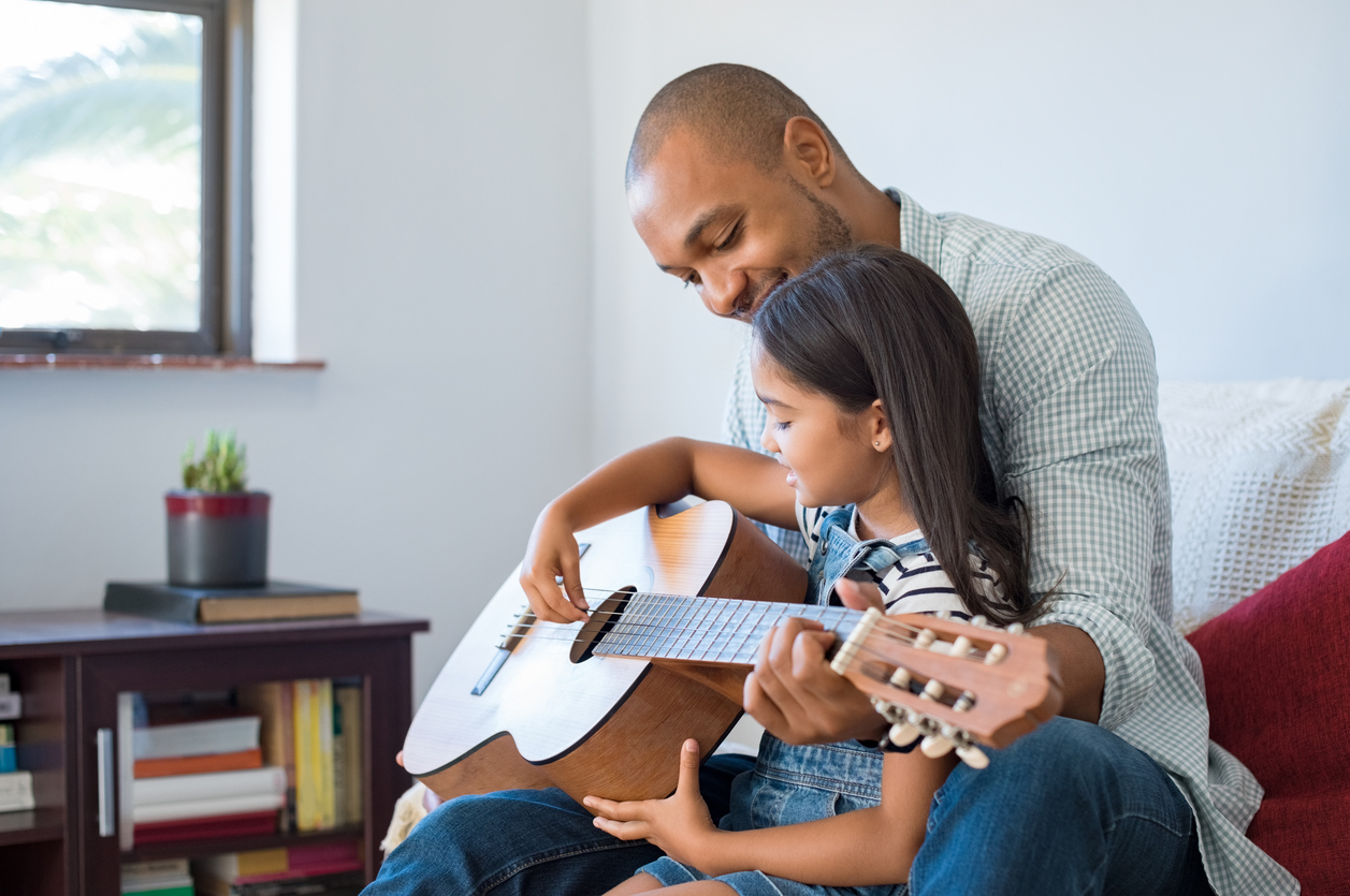 Father with adopted child after long-term fostering teaching her guitar