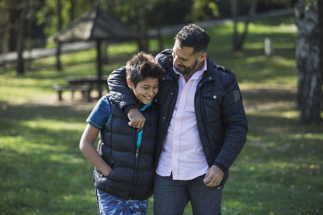Male fatehr figure hugging his foster child in support of foster care