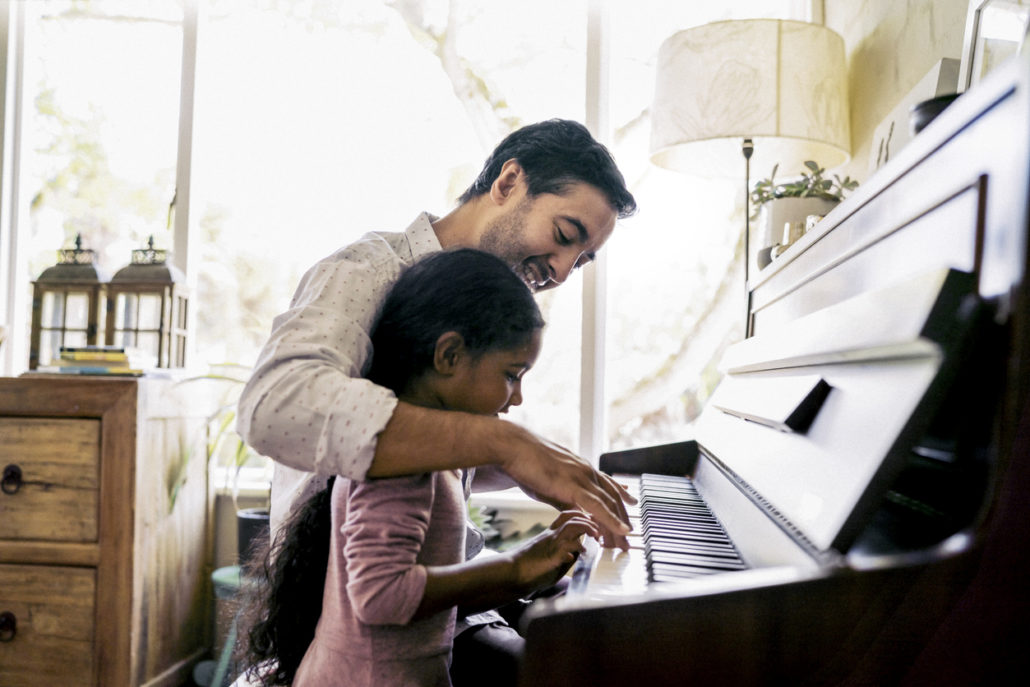 Man teaching his foster child to play piano after considering questions to ask before receiving his foster placement