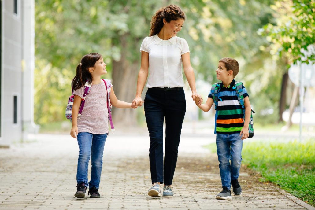 Woman walking her foster children to school, showcasing the reality of fostering a child