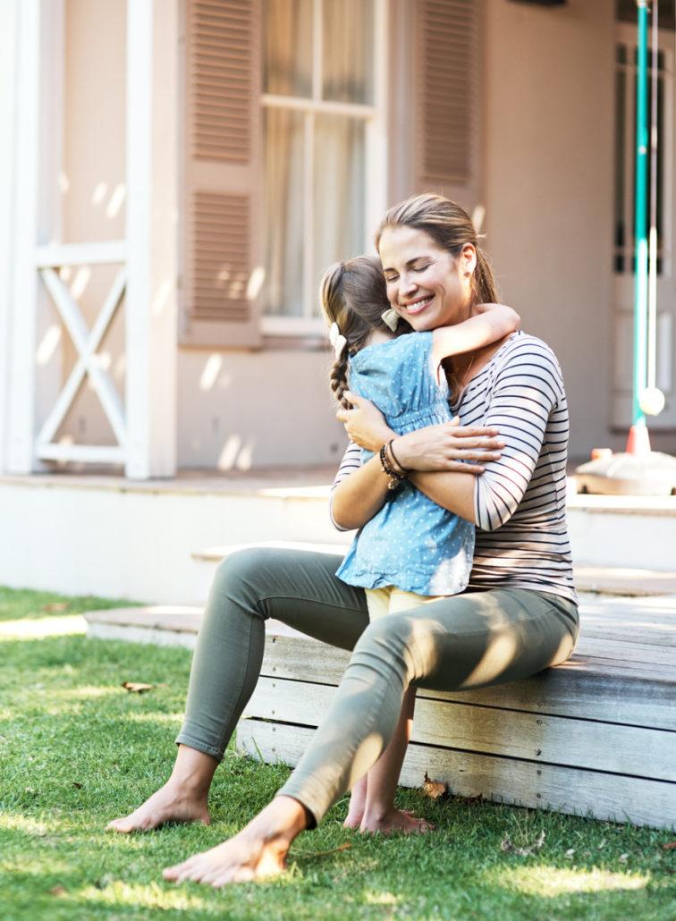 Foster family hugging in backyard