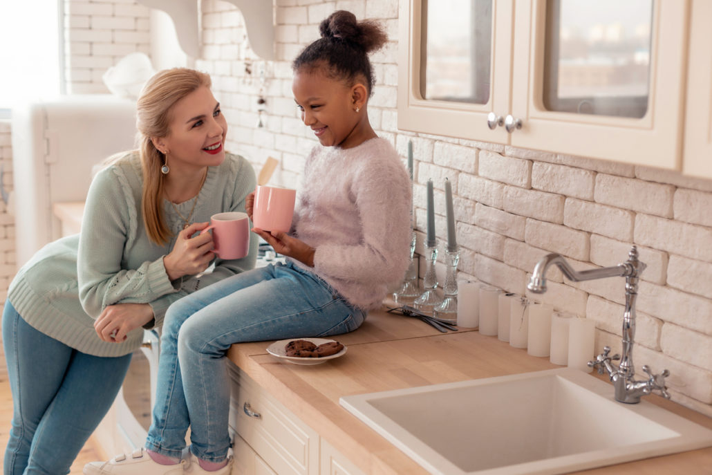 Mother and daughter in kitchen discussing adoption blogs
