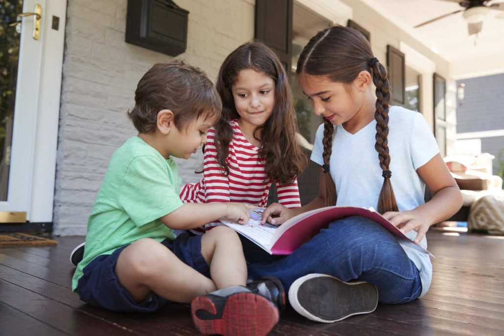 Group of children sitting on porch reading a book together at one of the sibling homes