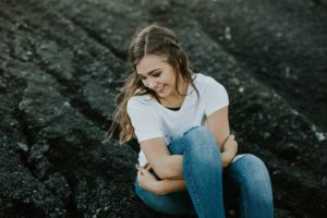 teenager sitting on rocks smiling away from the camera
