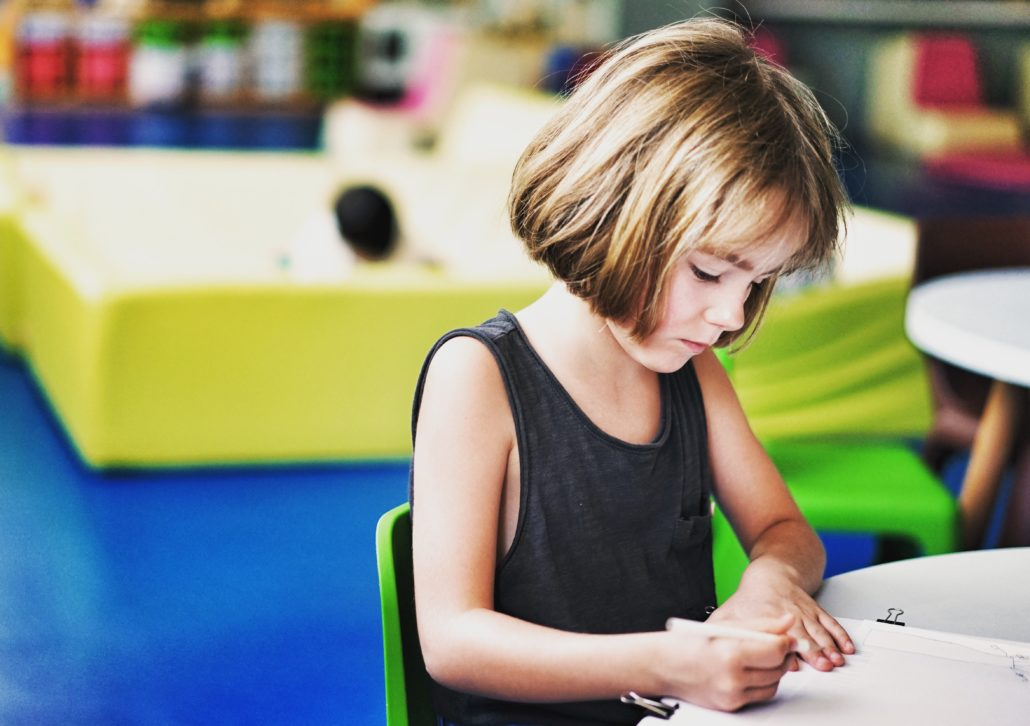 foster care child writing at her desk