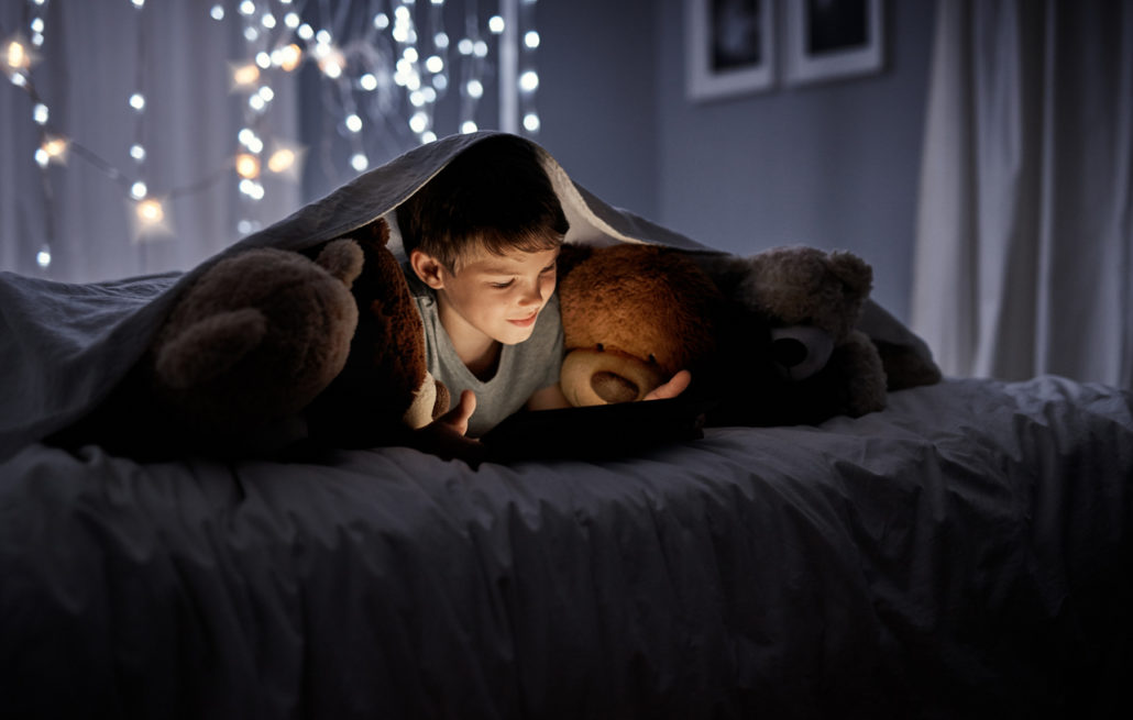 a foster child in his bedroom reading at night