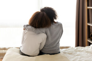 Foster mother and daughter in an embrace as rewards for fostering