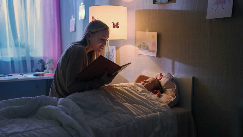 tucking a child into their own bed with a bedtime story